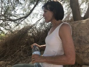 Woman pausing from her hike, for shade and a sip of water